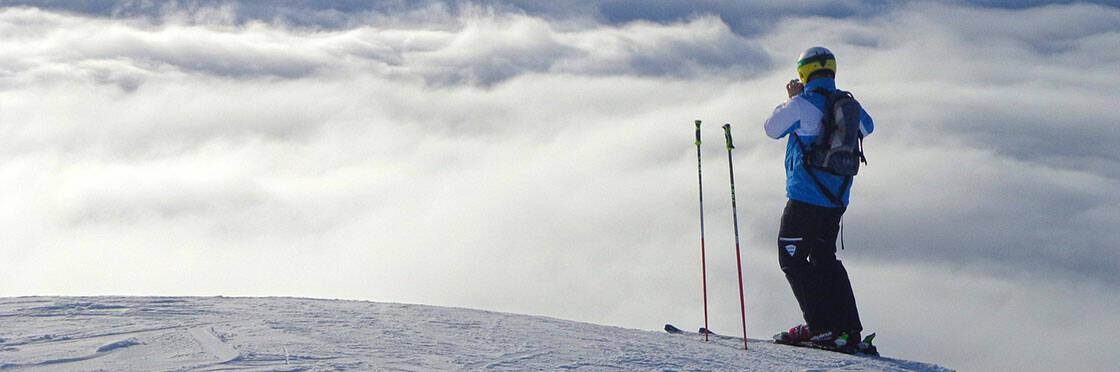 skieur prenant une photo au sommet d'une piste