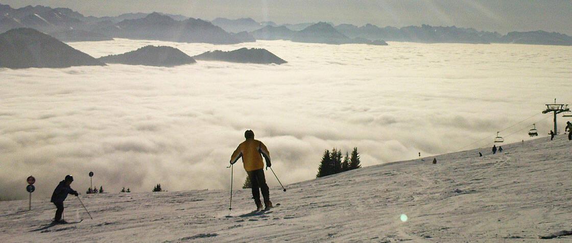 domaine skiable ensoleille au dessus des nuages