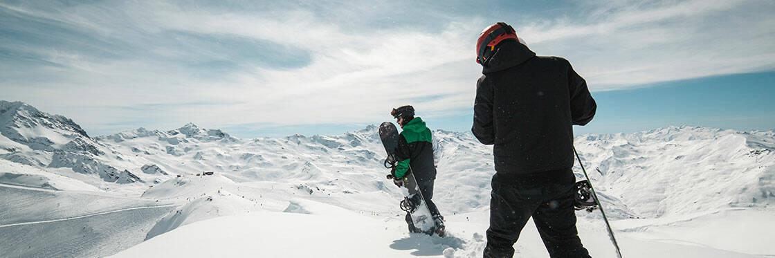 snowboardeurs qui marchent au sommet d'une montagne dans la poudreuse