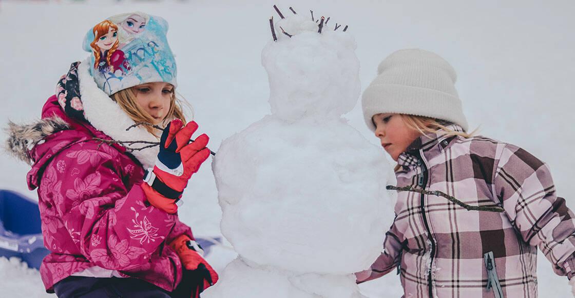 deux jeunes enfants qui font un bonhomme de neige
