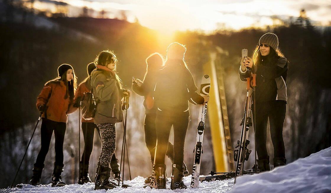 groupe de jeunes filles qui font une pause au bord d'une piste de ski