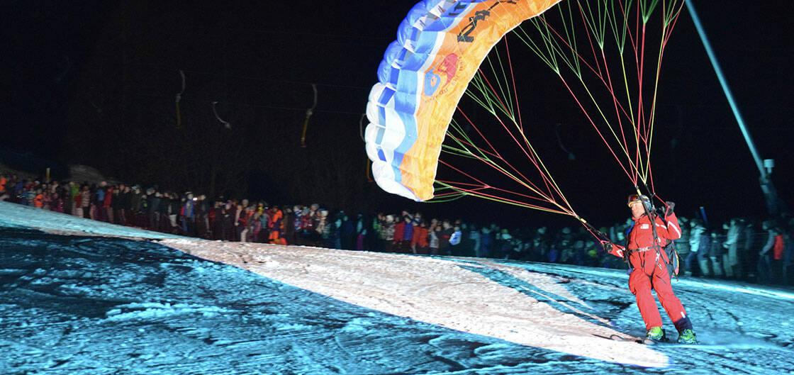moniteur esf qui atterrit sur une piste de ski en parapente