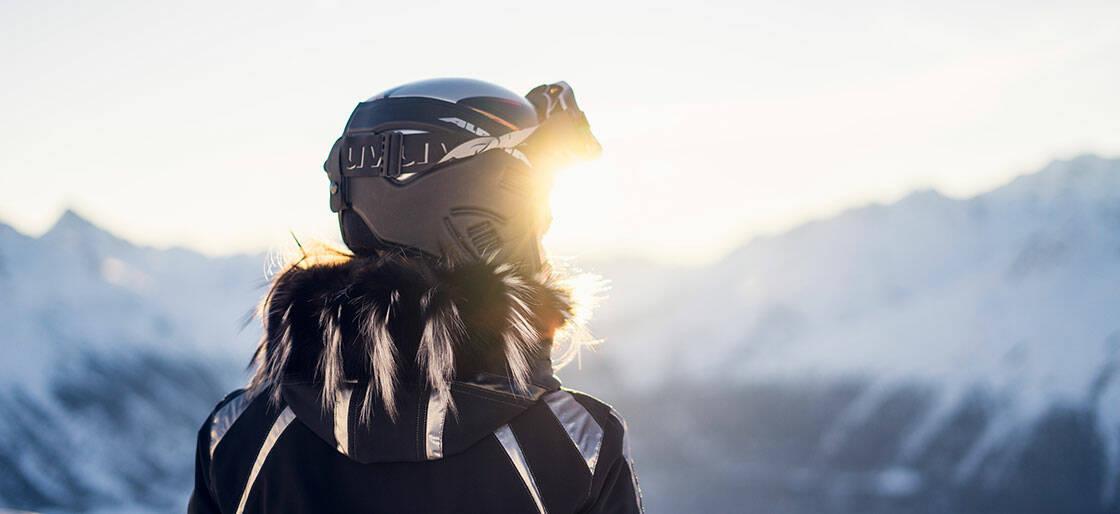 vue de dos d'une femme face à la montagne, qui porte un casque de ski