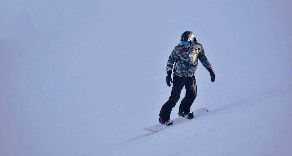 homme qui descend une piste en snowboard
