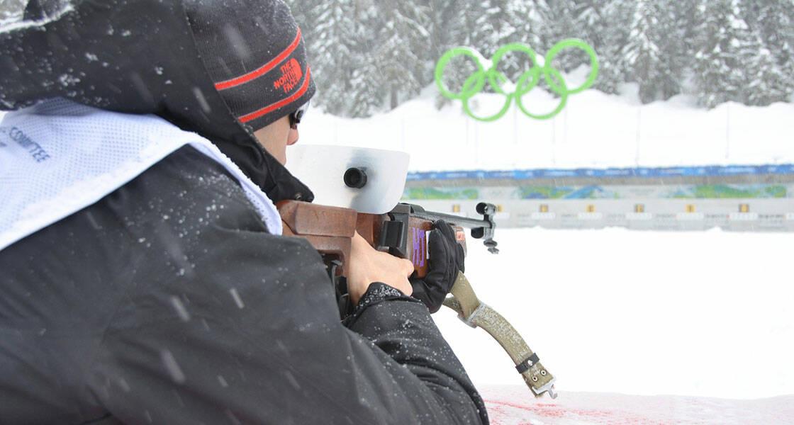 homme tirant à la carabine au stand de biathlon
