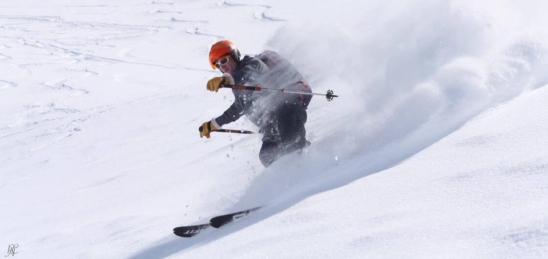 homme qui descend à ski dans la neige poudreuse